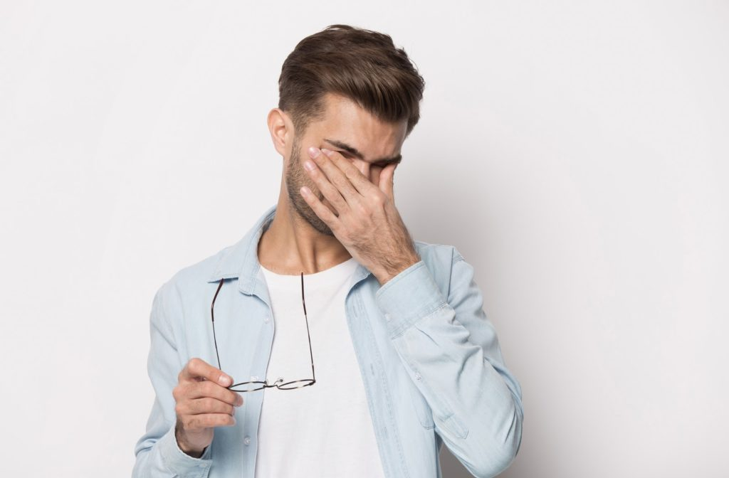 Man holding both of his eyes in pain because he is suffering from dry eye syndrome