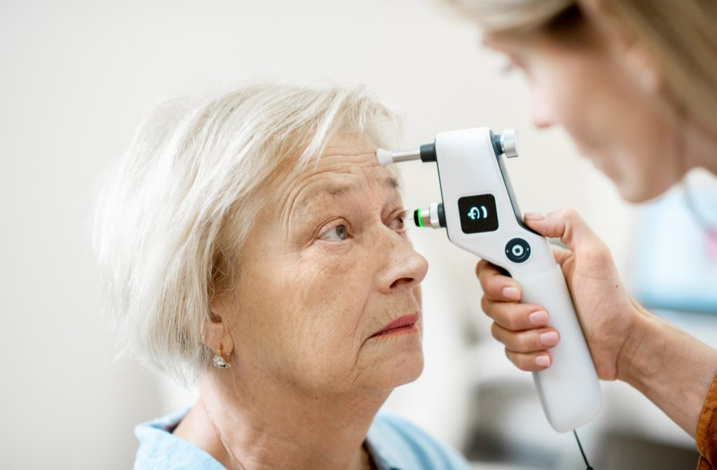 Elderly woman getting her eye's intraocular pressure measured by an ophthalmologist using a modern tonometer