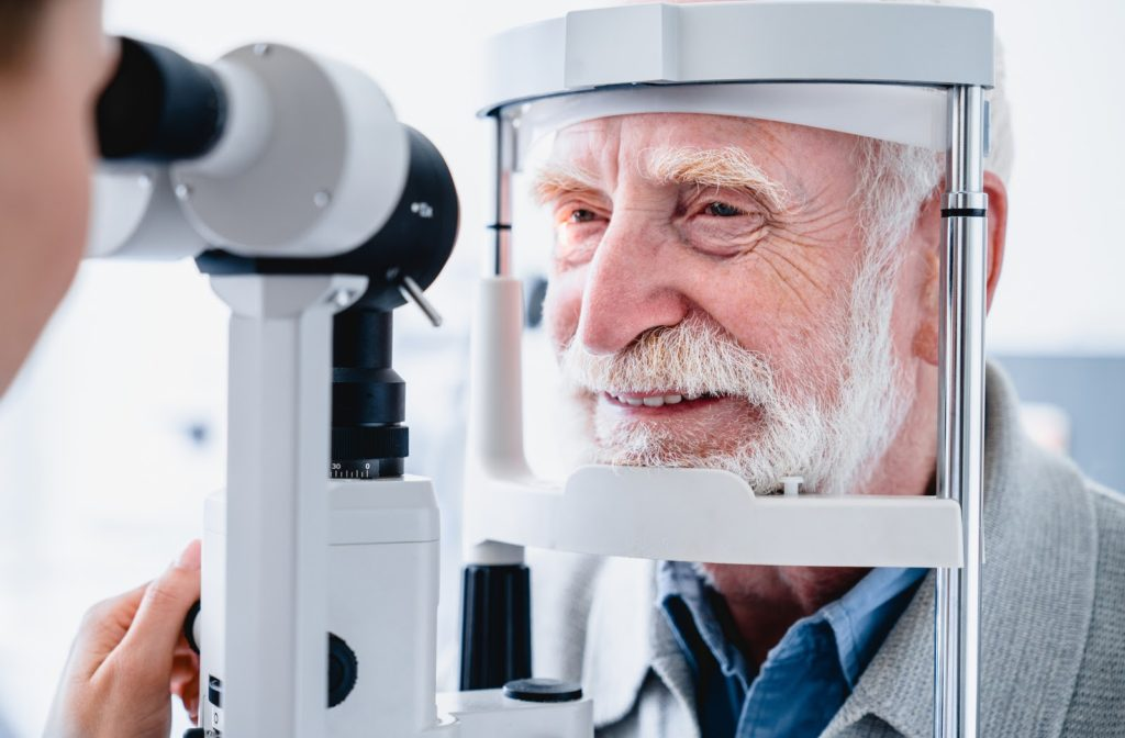 A smiling senior male patient getting an eye exam to look for glaucoma