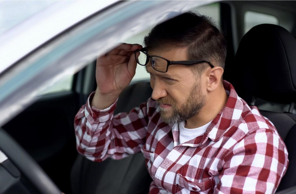 A driver with glasses suffering from blurry vision needing LASIK eye surgery to correct it