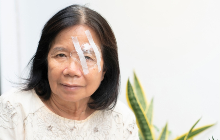 A woman sitting with a shield over her eye, protecting it after cataract surgery